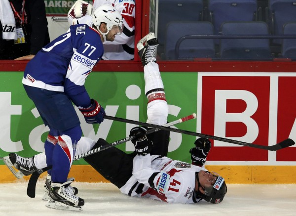 Austria's Altmann falls over from a body check by France's Treille during their 2013 IIHF Ice Hockey World Championship preliminary round match at the Hartwall Arena in Helsinki